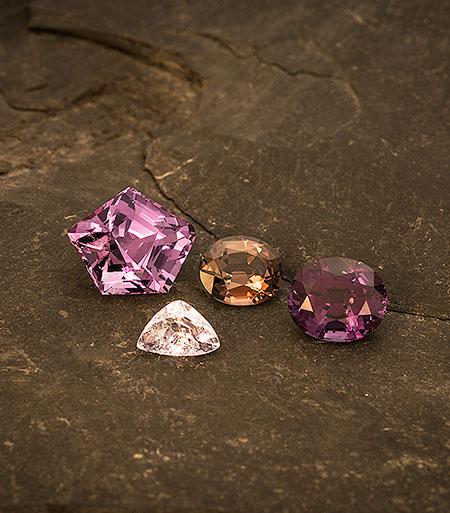 Fab four. From left, 8.50-carat purple pentagon from Sri Lanka (sold), 1.66-carat lavender trillion from Burma's Mogok Stone Tract ( #7805 ), 2.35-carat brown oval from Sri Lanka (sold), and 4.28-carat mauve oval from Sri Lanka (sold). (Photo: Mia Dixon)