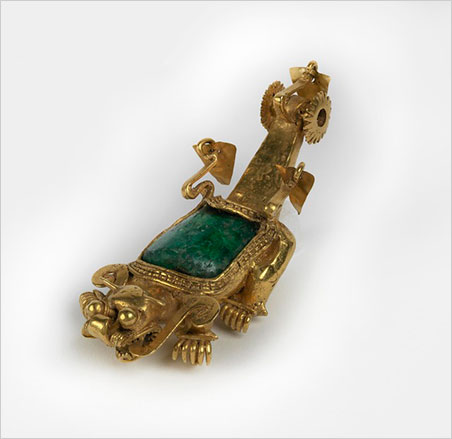 "Jaguar pendant.  Coclé culture, Sitio Conte, Coclé Province, Panama, AD 700–900. Large pillow-shaped emerald surrounded by four-part gold edging. Outer ones continuous, inner ones bead-like. Pair of decorative, sinuous, ""wings"" at back of emerald with loose, thin, moveable gold leaf attached. Four legs and feet projecting foreward, each with five similar curving claws, plus one beneath upcurving. Head with rude open mouth full of teeth above and below. Two flat tongues from mouth curving back and ending in scroll at neck. Very bulging eyes at top, almost spherical. Blunt nose with nostrils to sides consisting of four vertical fine-wire sections. Pair of short pointed horns (ears?) on top of head. Long raised tail of rectangular section ending in pair of fixed spiked ""wheels."" Between them a third wire with loose thin leaf ornament. Small attached horizontal tube between front legs for suspension on chest. This object was excavated in 1940 by J. Alden Mason, curator of the Penn Museum, after golden grave objects were exposed on the banks of the Río Grande de Coclé.   Click image to enlarge   (Photo courtesy Penn Museum)"