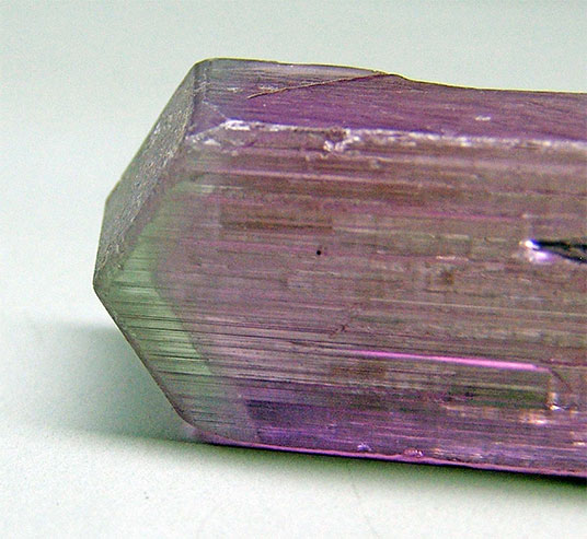 Figure 2.  Phantom-like purple kunzite crystal from Afghanistan, terminated by a pyramidal zone of light green colour. Weight 138.25 ct, width of green zone 2-3 mm. (Photograph by the author)
