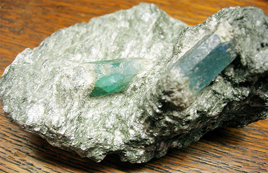 Figure 6.  Emerald and aquamarine crystals, separately embedded in a mica schist specimen from Habachtal, Austrian Alps. (Courtesy NHM Vienna)
