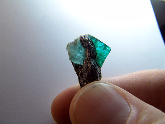 "Figure 8c.  A blue to blue-green Habachtal crystal chip. Another, more convincing ""emeraqua"" chip was sold at the Munich Mineral show 2010 (both pieces not available for analysis)."