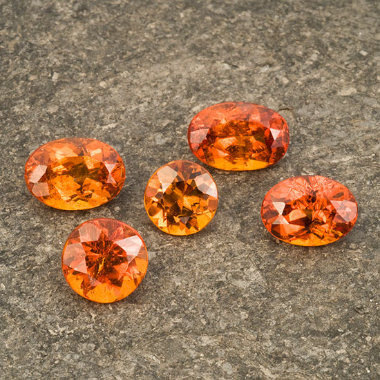 Hessonite garnets  from Baja California, Mexico. The three ovals total 4.63 ct and are part of seven stones in Inventory   #1551  . The round in the middle weighs 1.07 ct. The round at bottom left weighs 1.60 ct and is part of Bill Larson's personal Baja California collection. (Photo: Mia Dixon)