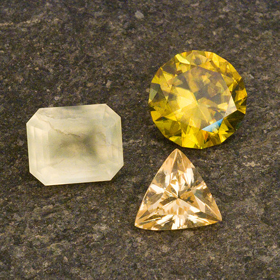 Un trío baja californiano.  Clockwise from left, yellowish-green prehnite weighing 3.21 cts, sphene from Pino Solo weighing 3.61 cts and a trillion scheelite from the El Fenomeno Mine, Sierra Juares, Baja California, Mexico. (Photo: Mia Dixon; Collection: Bill Larson)