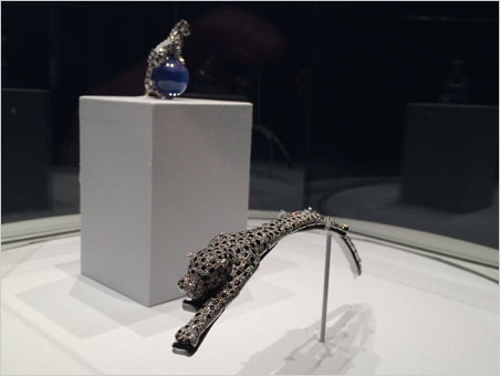 """Purr-fect. Some of the exhibition components are arranged thematically. Above, an articulated bracelet """"leaps"""" as a statuette looks on ( click  to enlarge). (Photos: Richard W. Hughes, top; David Hughes)"""