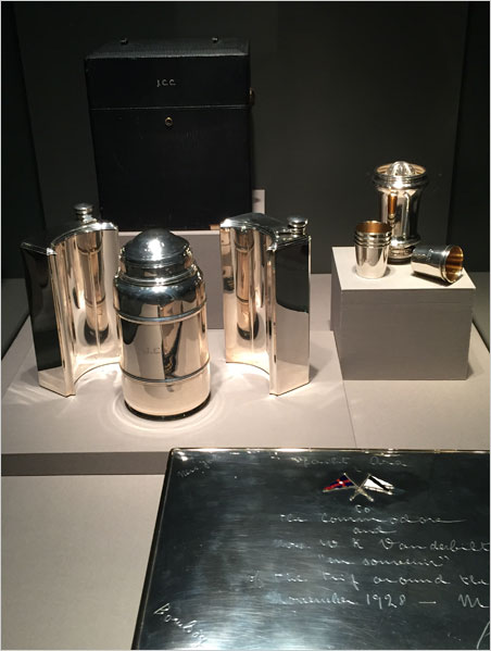"""Tippling, schooning and scribbling. Practical items also are included, such as the travel cocktail set above. Space-saving flasks for spirits surround the shaker. At back a citrus reamer with shot glasses. Upended, the reamer attaches to the shaker, making it long-necked, and acting as strainer. The tray is dedicated to William Kissam Vanderbilt II and his second wife, on the occasion of their trip around the world in 1928. (Vanderbilt was an avid yachtsman.) Vanderbilt is addressed in the inscription as """"Commodore,"""" a rank he appears to have shared with his great grandfather, Commodore Cornelius Vanderbilt, founder of the family fortune. Below, a pen with its own source of illumination, if not inspiration. (Photos: David Hughes)"""