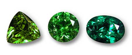 Three green gems, showing a variation in hue position. The round center stone is a straight green, while the trillion-cut stone at left is a more yellowish green and the oval stone at right a slightly bluish green. Generally speaking, hue position is of less importance than saturation. Photo: Wimon Manorotkul