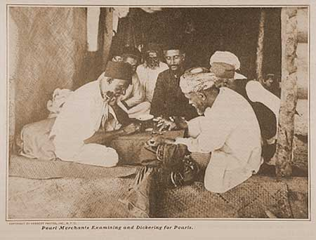 Pearl merchants examining and dickering for pearls