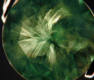 A classic example of a horsetail inclusion in a Russian demantoid garnet. (Photo:  Wimon Manorotkul  )