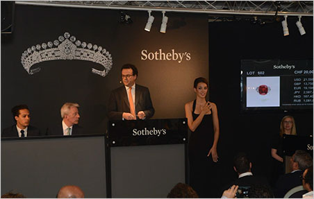 Going, going, going, going, going, going, gone.  Would the bidding ever stop? Above, David Bennett, Worldwide Chairman of Sotheby's International Jewellery Division, fields bids at auction of the Sunrise Ruby in Geneva. (Photo: Sotheby's news release)
