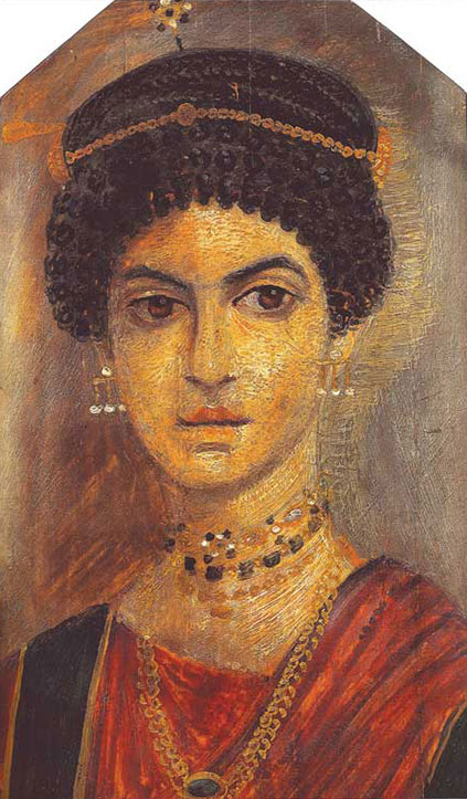 "The subject of this mummy portrait (110–120 C.E.) was named ""The Jewellery Girl"" by Egyptologist Flinders Petrie, who excavated the portrait at the archaeological site of Hawara in Egypt's Fayum Basin, southwest of Cairo (Walker 2000, 52). In her coiffure, the sitter wears a hairpin of pearls and garnets. The topmost necklace matches the hair ornament, but includes other stones that may be aquamarines or sapphires. Below that, a necklace and plaited chain both feature emeralds."
