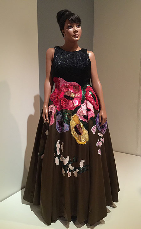 """Todd Oldham (United States), evening dress. Special order, 1997. Silk/rayon satin blend, glass beads, plastic sequins, synthetic trim. Appeared in 'The Jazz Age of Fashions.' From the caption placard: """"Dominated by the slender, fashion's runways hold little regard for real body types. After appeals from the Fashion Fair audience, [director Eunice Walker] Johnson began to include shapelier models. She custom ordered this stunning Oldham in a plus size. The shiny black beaded bodice and colorful floral embroidered skirt skillfully flatter a generous form."""" (Photo: David Hughes)"""