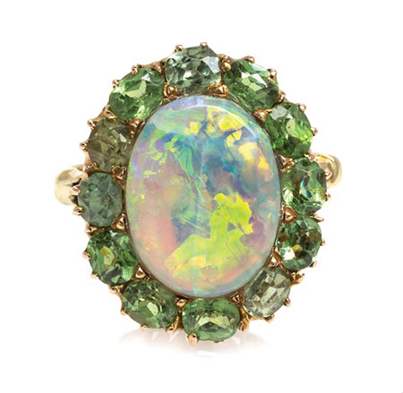 Lot 33  from the Bass Coors collection is a gray opal (12.28 x 9.35 mm) surrounded by twelve oval mixed-cut demantoid garnets of varying hues. (Photo courtesy Leslie Hindman Auctioneers)