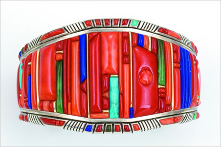 Bracelet.  Raymond C. Yazzie, 2005. Silver inlaid with coral, turquoise, lapis lazuli, 14-karat gold accents. 2 3/8 x 1 in. Collection of Mark and Martha Alexander. (Photo: Michael S. Waddell)