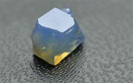 """No yellow sapphire samples were amongst those received by the laboratory, but yellow is observed via the Tyndall effect in GIA reference sample 100309934811. The sample was placed on a slightly reflective background and a white """"daylight"""" type fluorescent illumination illuminated it from above. As can be seen, blue color is scattered from the sides of the sample but when light reaches the lower part of the stone it becomes greenish and then yellow as most of the blue is scattered away. (Photo: Vincent Pardieu © GIA)"""