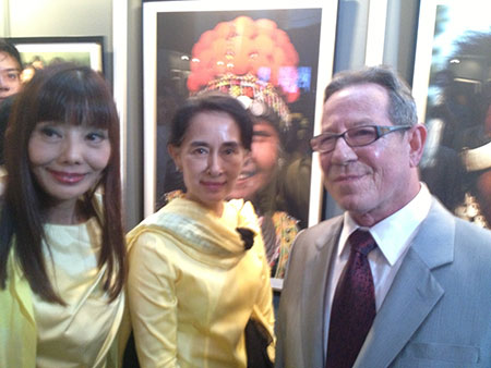 """"""" The Vanishing Tribes of Burma ,"""" an exhibition of photographs by Richard K. Diran, has found a permanent home in Yangon's National Museum, according to Mizzima News, October 12. Diran is a longtime friend of Pala International's Bill Larson, who snapped this photo of Daw Aung San Suu Kyi after meeting her at the reception for Diran, right, a year ago. (Photo: Bill Larson)"""