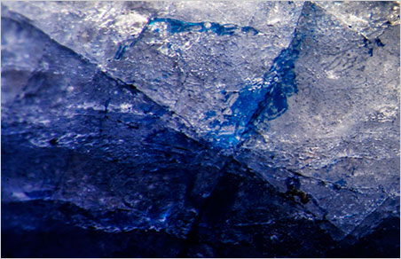 Blue cobalt-doped glass fills a surface-reaching fissure in this first-generation stone. Oblique fiber-optic illumination. The color in such near-colorless stones is obtained almost exclusively from the filling. (Photomicrograph: Wimon Manorotkul)