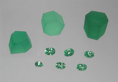 Rough and cut V-bearing synthetic chrysoberyl grown by Kyocera Corporation. The top-right piece weighs 10.5 g and measures 15.5 × 15.5 × 14.4 mm; the faceted samples weigh 0.49–1.33 ct. (Photo: Karl Schmetzer)
