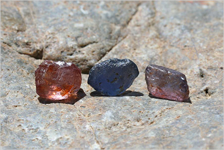 Rough sapphire…?  The unidentified dumortierite on the left before cutting, alongside actual sapphires.
