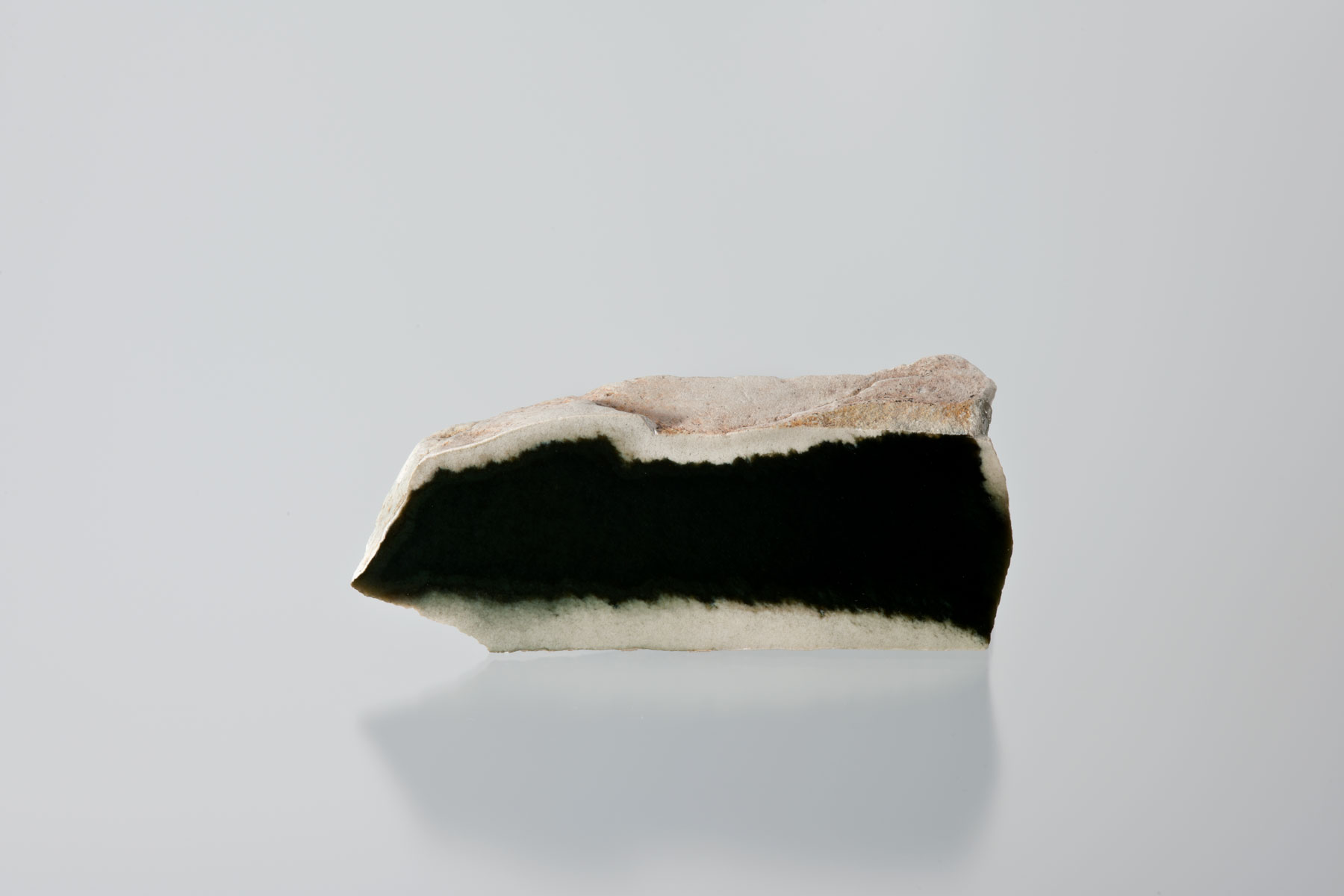 "This 3-lb cut piece of black jade shows the 1/3"" of soft white rind that is often found in mined black jade. The quality of red-rind black jade and white-rind black jade is the same in most cases.  (Photo: Robert Weldon)"