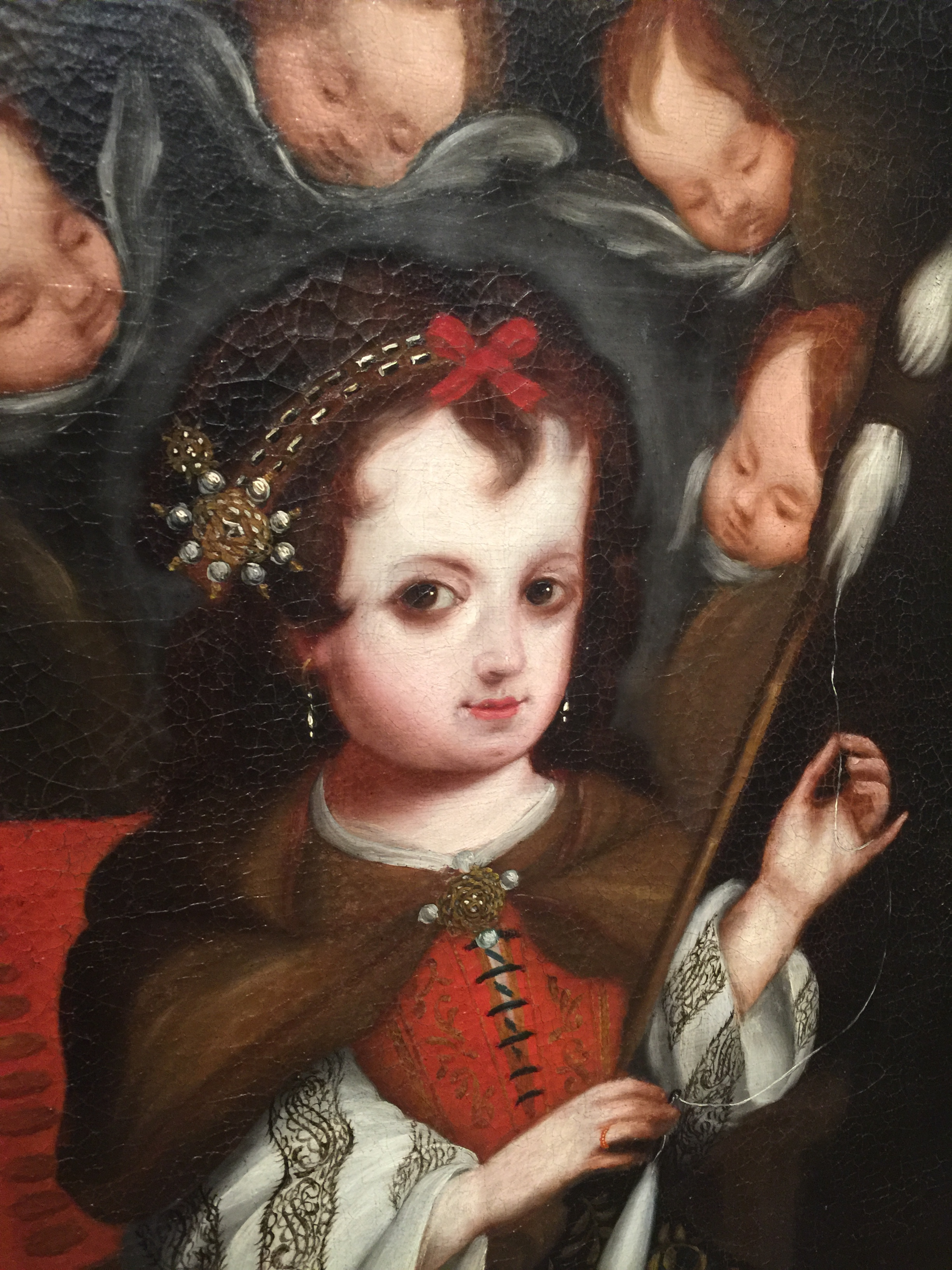"Even the Virgin Mary, pictured above as a child spinning yarn, is a cultural hybrid. ""Her cloak, held together by a circular jewel, recalls both Spanish capes and the Inca  lliclla  mantle fastened by a  ttipqui  pin,"" according to the painting's title card. From Spain, about 1700, oil paint on canvas (detail). Gift of Engracia Freyer Dougherty for the Frank Barrows Freyer Collection; 1969.353. (Photo: David Hughes)"