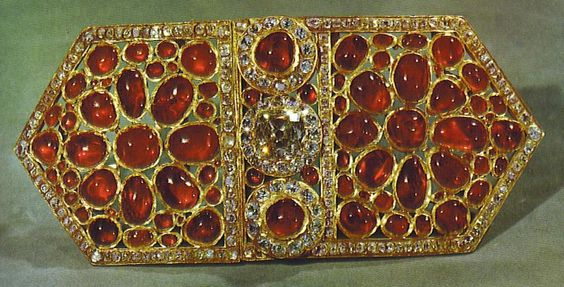 Buckle.  This buckle contains 84 cabochon-cut Burmese rubies, the two largest weighing an estimated 11 carats each. The cushion-cut brilliant diamond is a pale yellow (est. 17 ct).