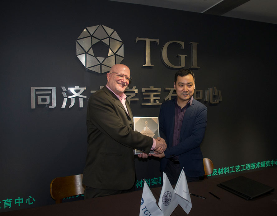Richard W. Hughes smiles after signing the formal agreement for honorary professorship with Tongji University's Zhou Zhengyu (Adam). Adam is the director of the Laboratory of Gems and Technological Materials, School of Ocean and Earth Sciences, Tongji University, Shanghai. (Photo: E. Billie Hughes)