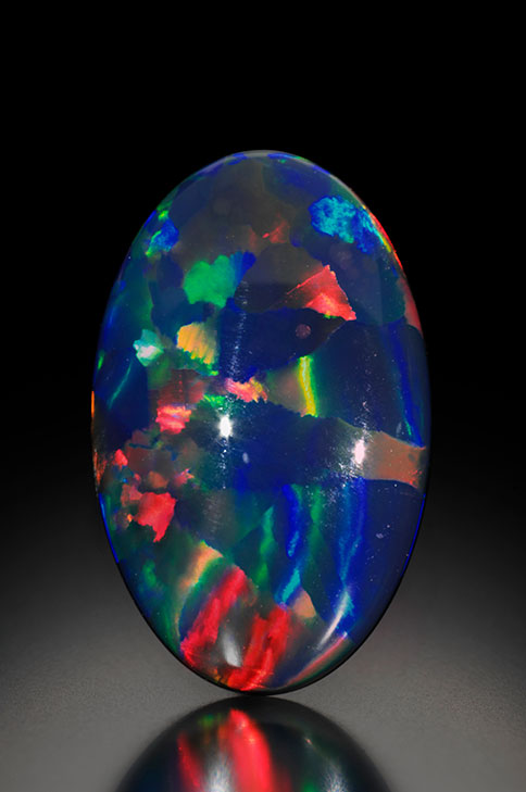 "Borealis , a rare Lightning Ridge black opal. This is a red multicolor opal of the rare harlequin pattern (N1-N2). ""One of the finest harlequins ever found,"" says Richard Wise in describing this gem from the Cora N. Miller Collection. (Photo: Jeff Scovil, courtesy R. W. Wise, Goldsmiths)"