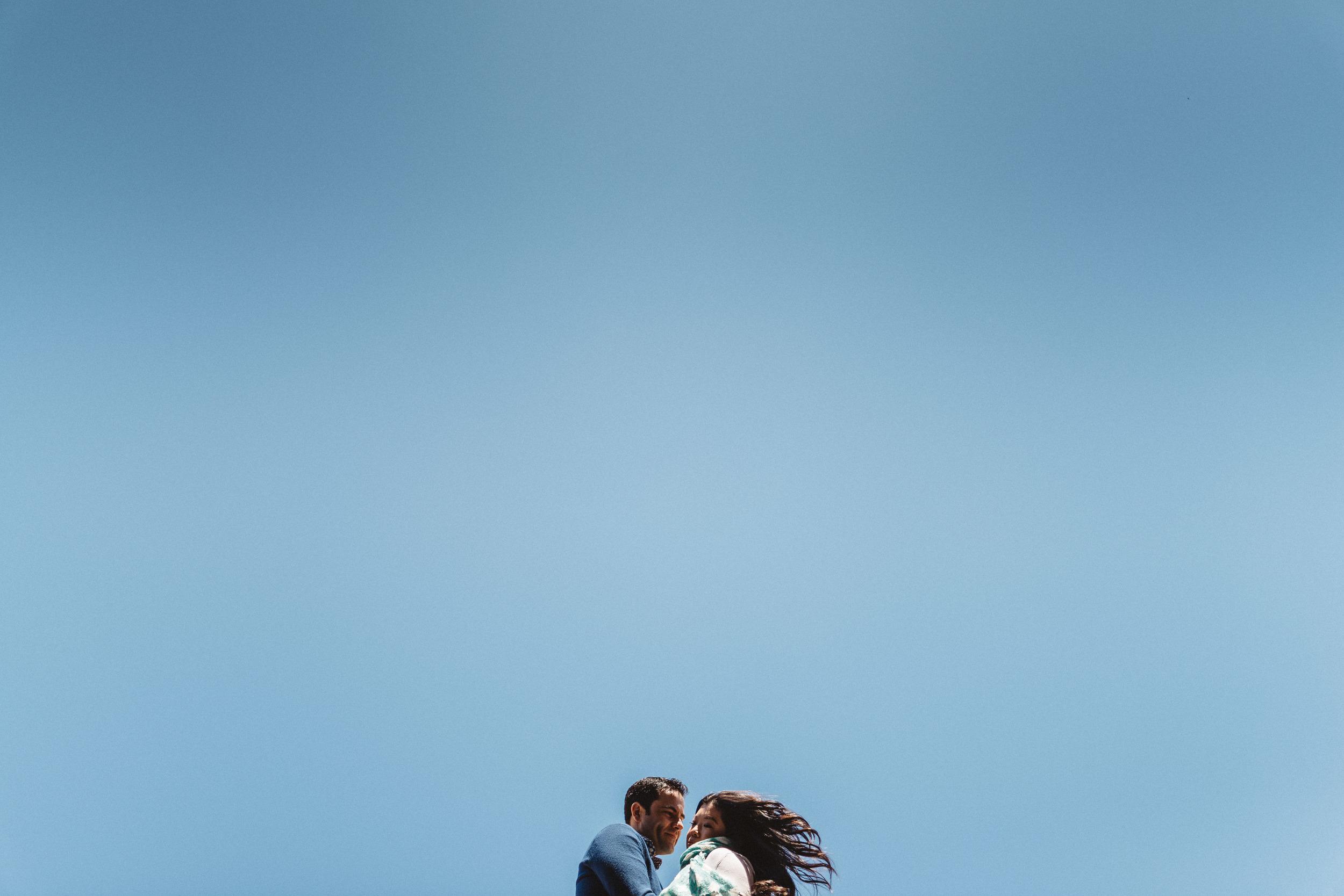 Happy engaged couple posing for artistic, minimalist, epic portrait