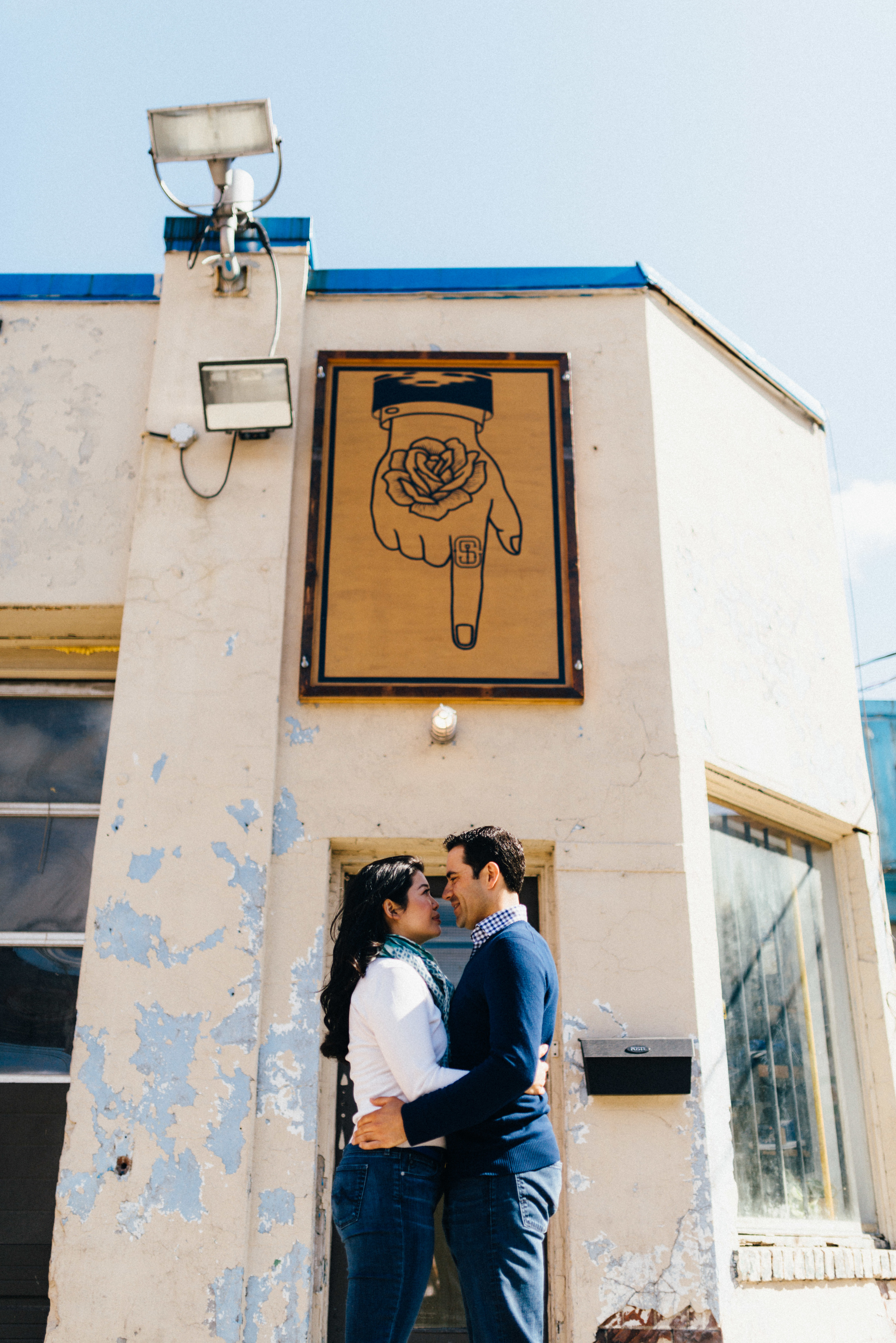 Another creative, funny photograph of couple below sign