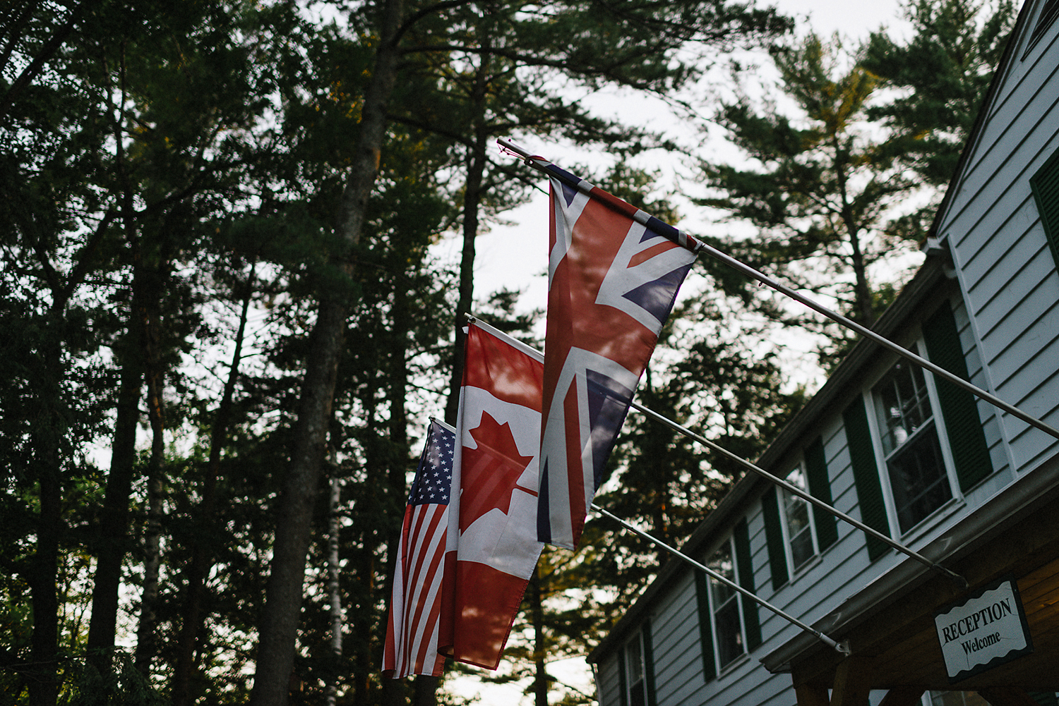 Muskoka-Cottage-Wedding-Photography-Photographer_Photojournalistic-Documentary-Wedding-Photography_Lakeside-Ceremony-Sunset-Light-on-flags.jpg