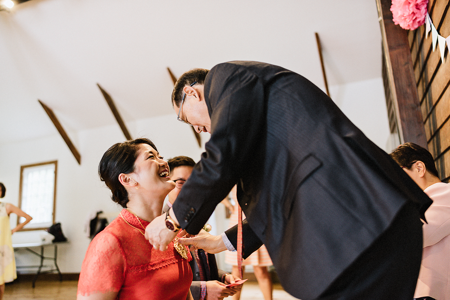 Chinese-Tea-Ceremony-in-outdoor-forest-venue-toronto-high-park-colbourn-lodge-dog-friendly-venue-bride-and-groom-candid-moment-best-documentary-wedding-photographers-Chinese-Tea-Ceremony-Candid-Moment-father-of-bride-giving-gift.jpg
