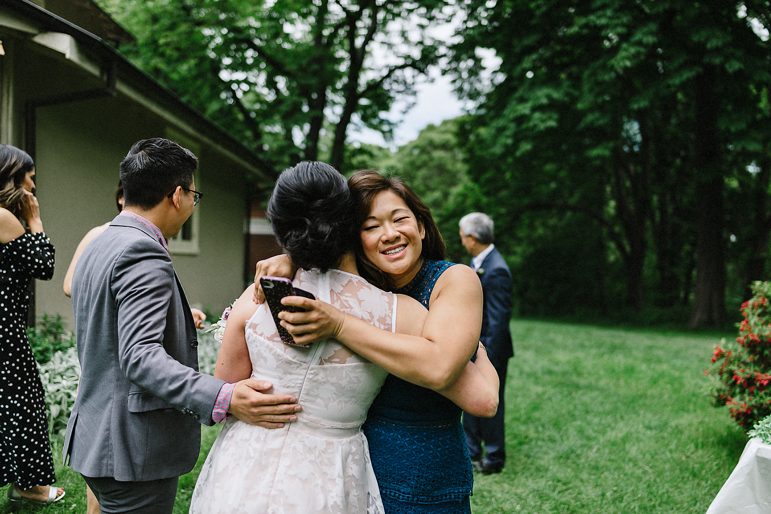 Outdoor-CeremonyIdeas-Bride-and-Groom-Exit-Toronto-Vintage-Bride-Outdoor-Forest-Wedding-Venue-High-Park-Downtown-Toronto_Candid-Editorial-Documentary-Wedding-Photographers-Sweet-Candid-Moment-Between-Groom--and-Bride-Hugging-Sister.jpg