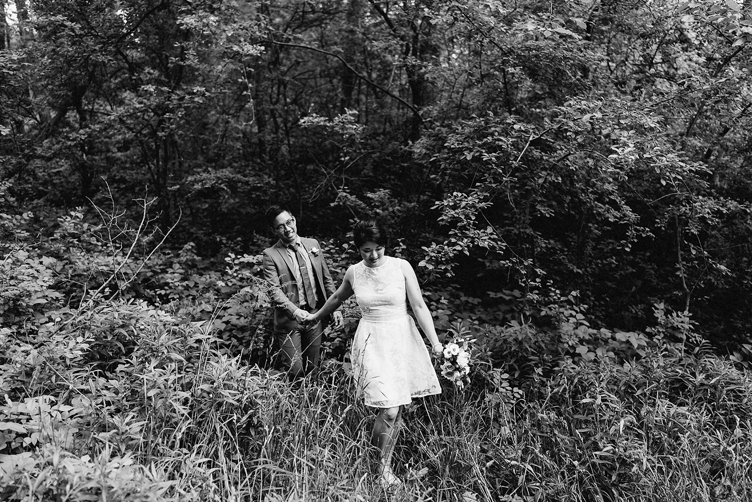 Fine-Art-Documentary-Wedding-Photographer-Toronto-Ontario-Canada_-High-Park-The-Lodge-Outdoor-Forest-Wedding_-Candid-moment-between-bride-and-groom--Lost-in-Forest-Trees-Epic-Candid-Moment-walking-among-trees.jpg