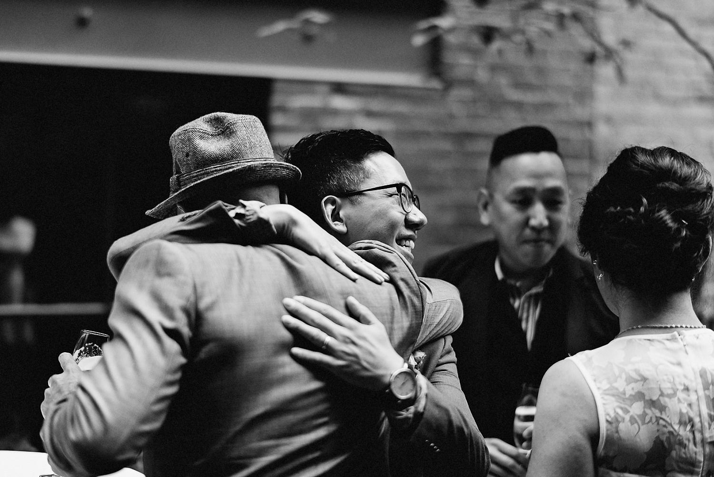 Best-Toronto-Wedding-Photographers_High-Park-Wedding_The-Lodge-Wedding_George-Restaurant-Reception_Analog-Film_Intimate-Candid-Photography_Guests-Detail_Outdoor-Summer-Wedding-Toronto_Casual-Restaurant-Wedding-candid-Groom-hugging.jpg
