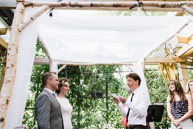 urban-downtown-toronto-wedding-fat-pasha-torontos-best-wedding-photographer-3b-photography-film-photographer-analog-photography-ceremony-on-outdoor-patio-kodak-portra-800-bride-and-groom-listening-to-friends-do-readings.jpg