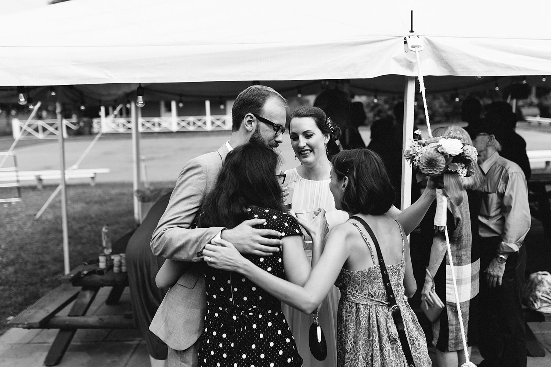 Toronto-Island-Wedding-Toronto-Best-Film-Wedding-Photographers-3b-photography-analog-photography-wards-island-clubhouse-junebug-weddings-vintage-venue-reception-cocktail-hour-hugging-congratulating.jpg