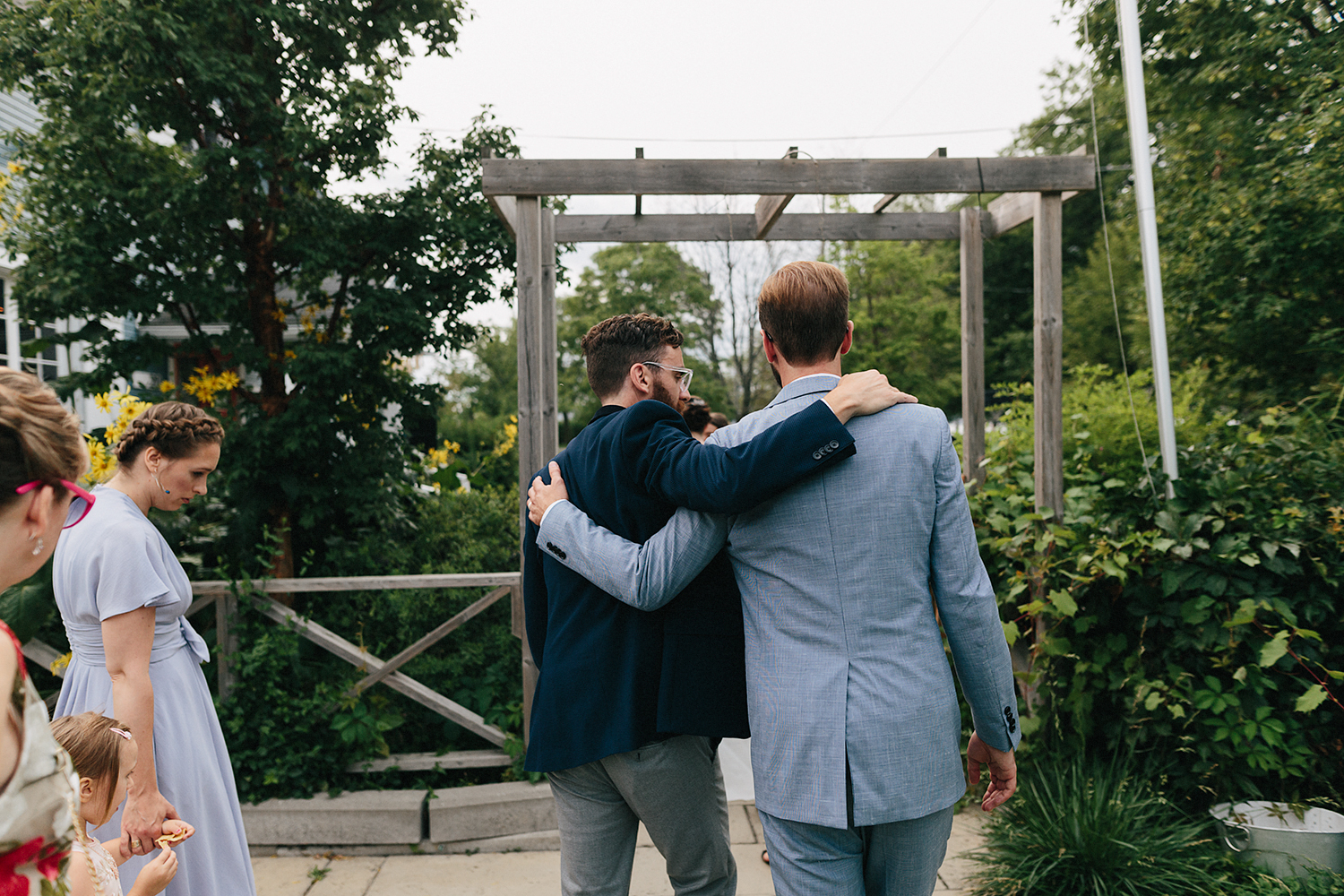 Toronto-Island-Wedding-Toronto-Best-Film-Wedding-Photographers-3b-photography-analog-photography-wards-island-clubhouse-junebug-weddings-vintage-venue-reception-cocktail-hour-candid-guests-mingling-hugging-groom.jpg