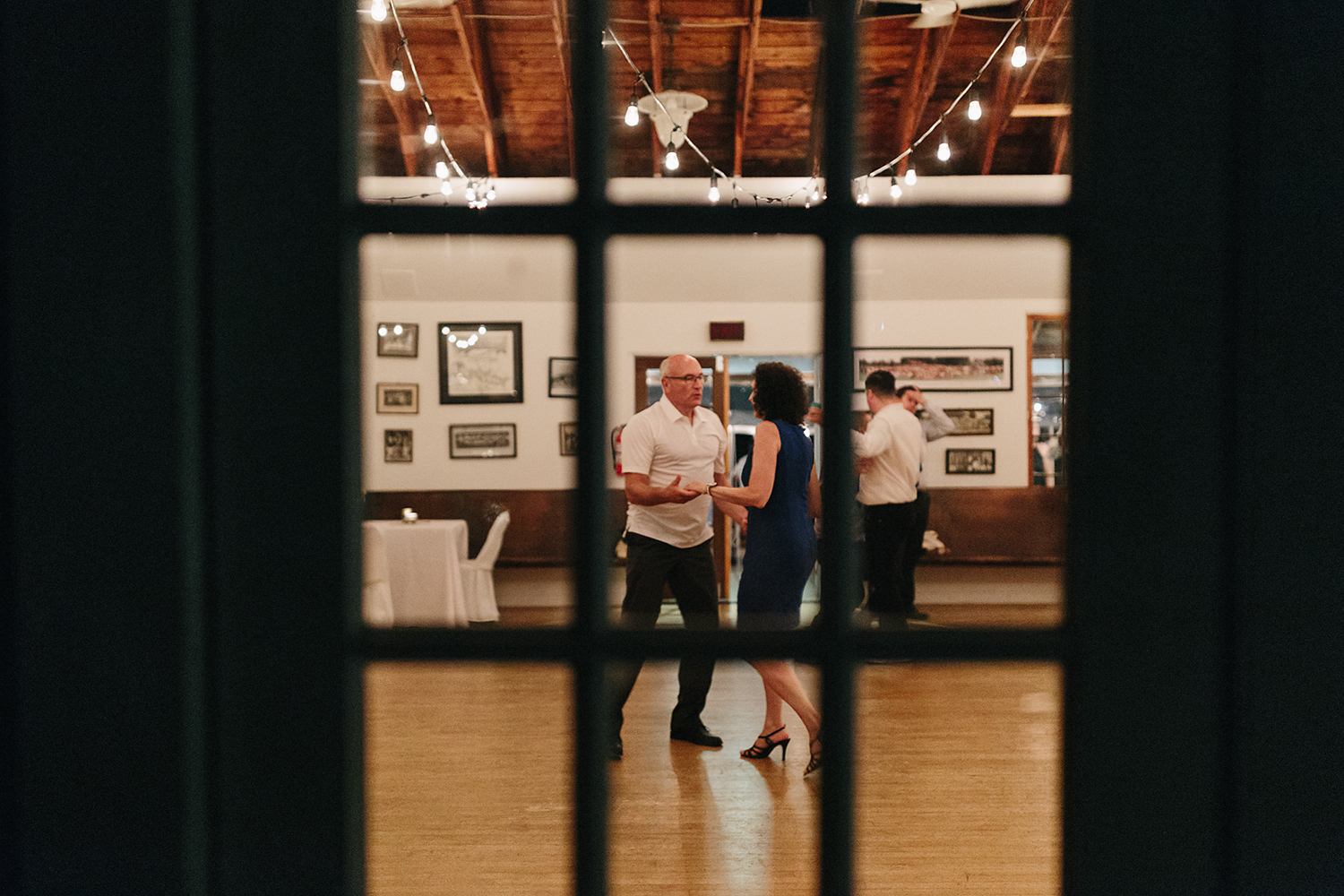Best-Film-Wedding-Photographers-3b-photography-analog-photography-wards-island-clubhouse-junebug-weddings-vintage-venue-reception-guests-dancing-candid-moments-memories-through-window.jpg