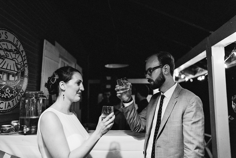 Toronto-Island-Wedding-Toronto-Best-Film-Wedding-Photographers-3b-photography-analog-photography-wards-island-clubhouse-junebug-weddings-vintage-venue-reception-cocktail-hour-candid-guests-mingling-bride-cheers-whiskey.jpg
