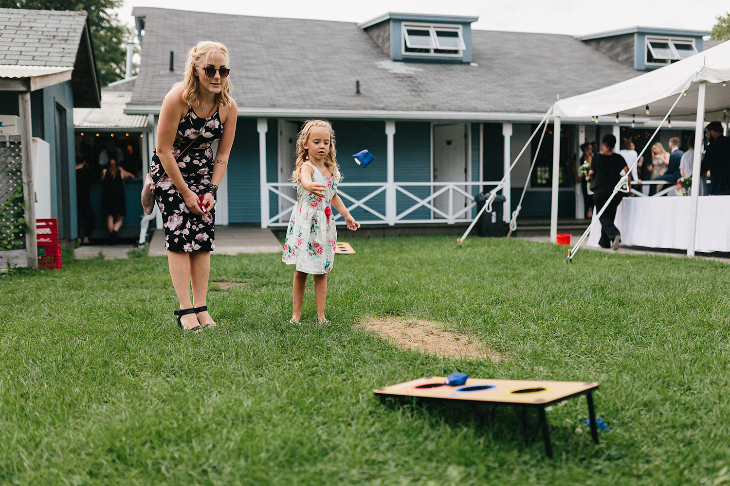 Toronto-Island-Wedding-Toronto-Best-Film-Wedding-Photographers-3b-photography-analog-photography-wards-island-clubhouse-junebug-weddings-vintage-venue-reception-cocktail-hour-candid-guests-mingling-girl-playing-lawn-games-cornhole.jpg