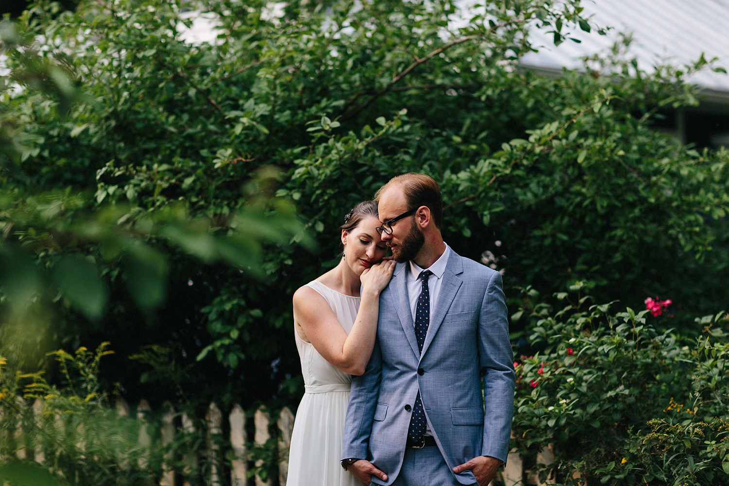 Toronto-Island-Best-Film-Wedding-Photographers-3b-photography-analog-photography-wards-island-clubhouse-green-wedding-shoes-vintage-venue-bride-and-groom-photos-intimate-photo-locations-in-nature-trees-greenery-houses-hug.jpg