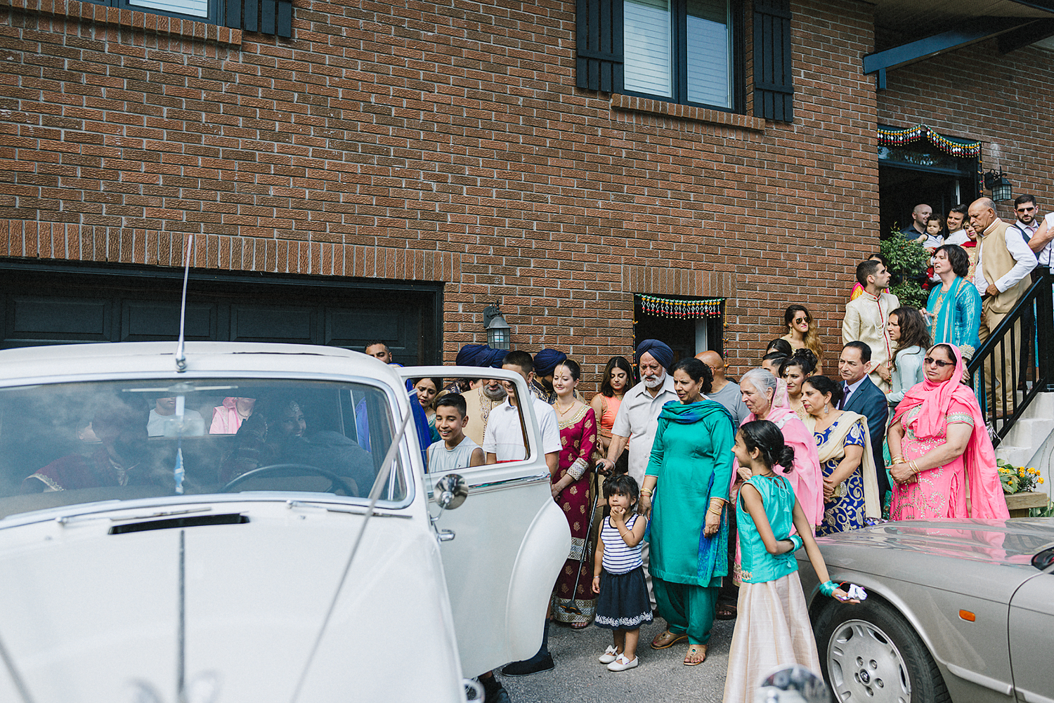 Toronto-Photojournalism-wedding-photographers-3B-Photography-Candid-Documentary-Film-Photography-Analog-Ontario-Hamilton-Port-Perry-Venue-Groom-Getting-Ready-putting-on-turban-sikh-ceremony-bride-entire-family-seeing-her-off.jpg