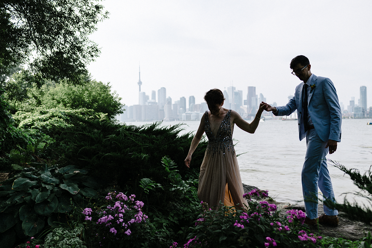 Bride-and-Groom-Sharing-Quiet-moment-looking-at-sunset-over-toronto-skyline-toronto-wedding-photographers-Toronto-island-Cafe-clubhouse-wedding-boho-hip-cool-bride-and-groom-walking.jpg