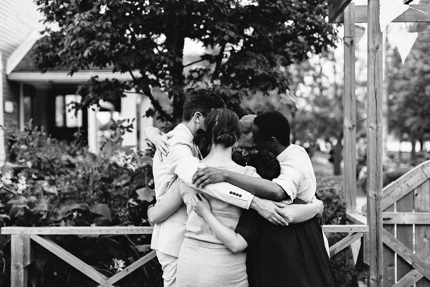 Best-Wedding-Photographers-Toronto-with-documentary-style-photojournalistic-wedding-photographer-editorial-cool-hip-timeless-Intimate-Toronto-Island-Cafe-Clubhouse-Wedding-groom-and-friends-hug.jpg