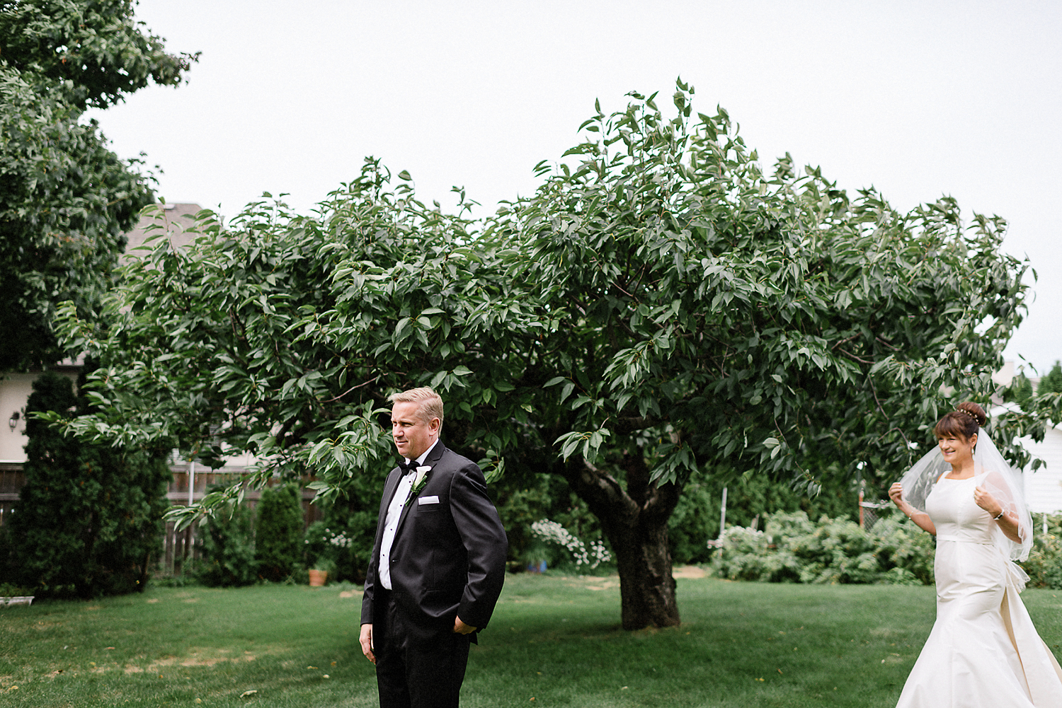 Best-Moody-Documentary-Wedding-Photographers-in-Toronto-Canada-Vintage-Photojournalistic-Wedding-photography-Epic-Moody-Cinematic-First-Look-in-Brides-Parents-backyard-by-cherry-tree.jpg