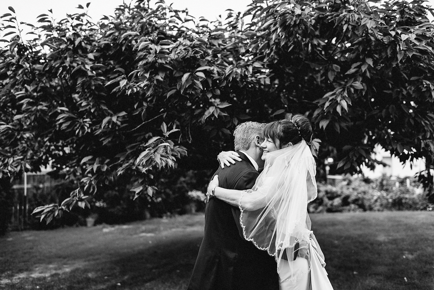 Best-Moody-Documentary-Wedding-Photographers-in-Toronto-Canada-Vintage-Photojournalistic-Wedding-photography-Epic-Moody-Cinematic-First-Look-in-Brides-Parents-backyard-kissing-BW.jpg