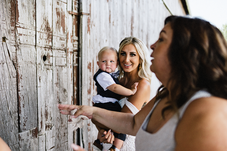 dowswell-barn-wedding-beaverton-best-wedding-photographers-toronto-moody-style-candid-photojounalistic-approach-intimate-vintage-farm-wedding-Farm-wedding-bride-candid-moment-with-baby-son.jpg