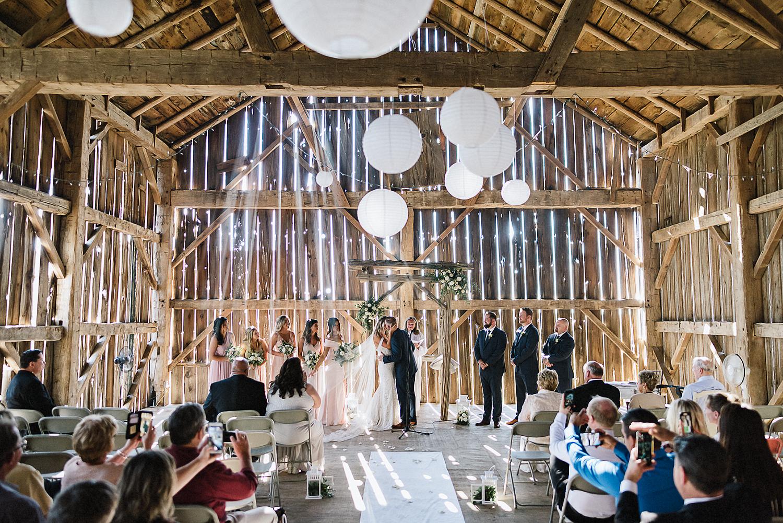 dowswell-barn-wedding-beaverton-best-wedding-photographers-toronto-moody-style-candid-photojounalistic-approach-intimate-vintage-farm-wedding-Farm-wedding-venue-details-ceremony-bride-and-groom-first-kiss.jpg
