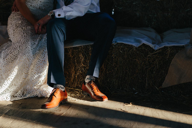 Documentary-Wedding-Photographers-in-Toronto-Candid-Natural-Dowswell-Barn-Wedding-Rustic-GTA-Muskoka-Farm-bride-and-groom-portrait-vintage-lace-veil-moody-sash-and-bustle-romantic-barn-golden-light-sitting-together.jpg