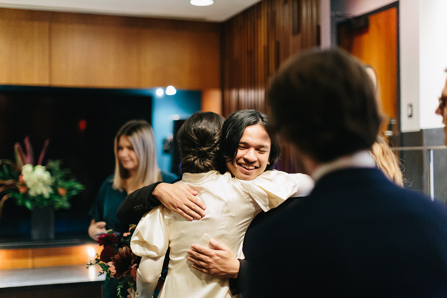 hugging-just-married-celebration-with-witnesses-candid-laughing-emotional-tattooed-bride-vintage-wedding-inspiration-bouquet-by-timberlost-Toronto-Elopement-at-the-Drake-Hotel-Torontos-Best-elopement-photographers-candid-documentary.jpg